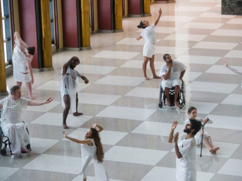 9 people are pictured in static elegant poses, dressed in white as part of a performance. Two of the people pictured are wheelchair user and another is holding a crutch
