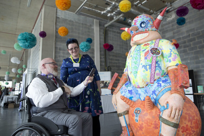 An old man in a wheelchair is taking a photo of an art sculpture of a man wearing shorts and braces on a space hopper.