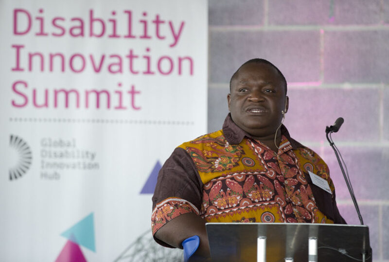 Man speaking at the Disability Innovation Summit, HereEast building.