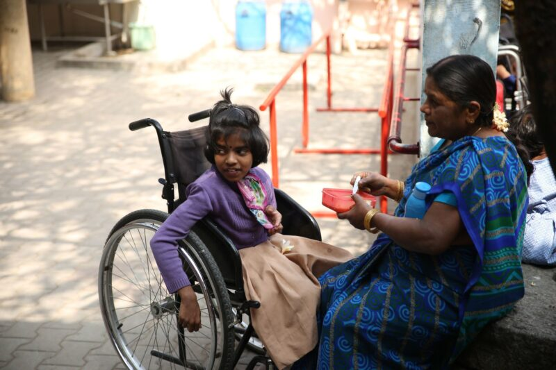 Photo of a young Indian girl on an oversized wheelchair being fed by her mother
