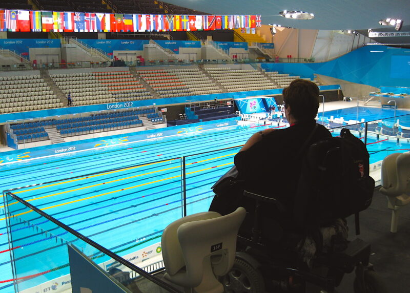 A photograph of Margaret surveying the Olympic and Paralympic pool from a viewing platform
