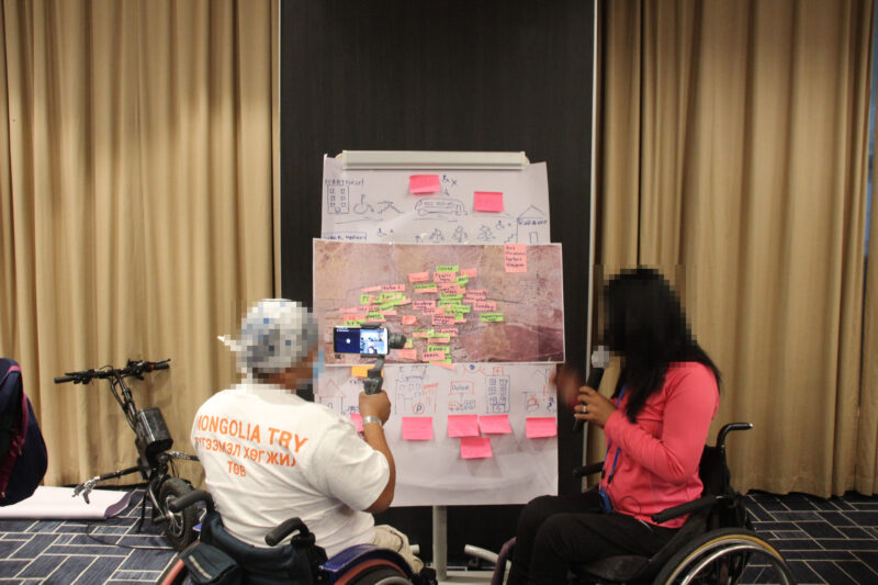 participatory workshop in Mongolia, two wheelchair users are presenting a map covered in coloured post-it notes which show design suggestions. One person is holding up a phone to stream the presentation virtually.