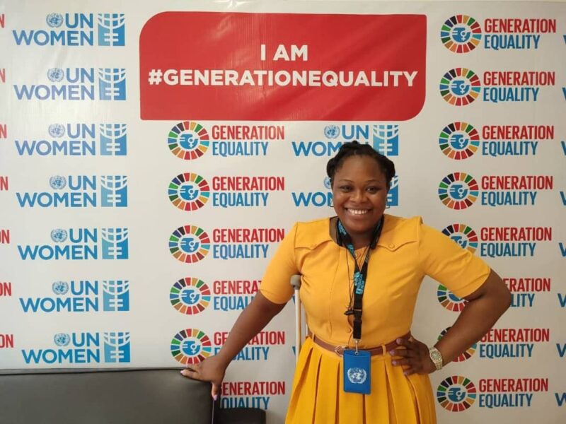 Uzoamaka is a black woman wearing a yellow dress, stood with one hand on her hip a crutch under her right arm. Uzoamaka is stood in front of a UN banner that says I am #GenerationEquality. She is smiling