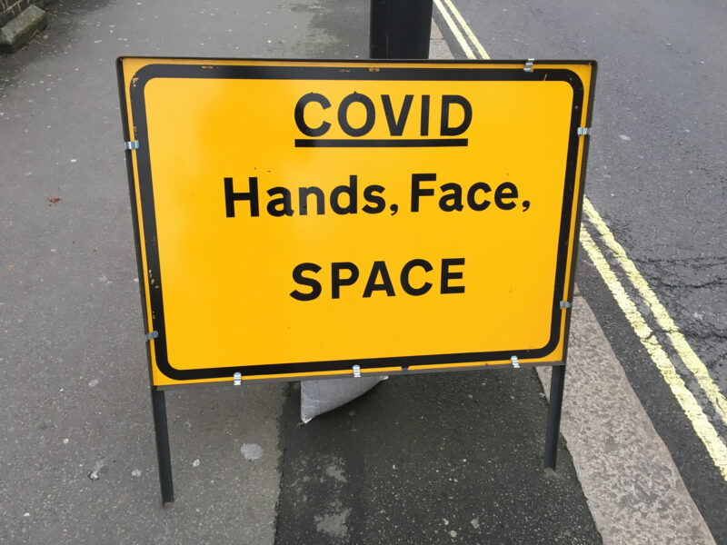 A black and yellow sign on the pavement that reads: Covid, hands, face, space