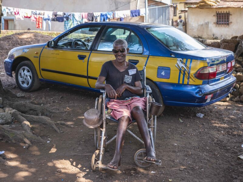 A man sat in a wheelchair in front of a taxi in the local village.
