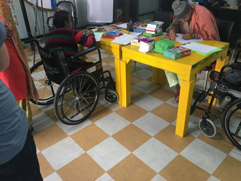 A wheelchair user facing away from camera at a bright yellow table full of art supplies, the floor is orange/red chequered pattern and there are two other people at the table. It looks like a classroom.