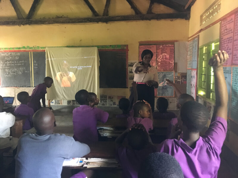 An ugandan boy in a full classroom raises his hand to ask something to teacher.