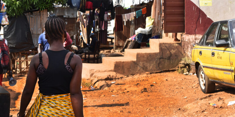 Woman walking up the road, towards some houses in Sierra Leone. It is a sunny day.
