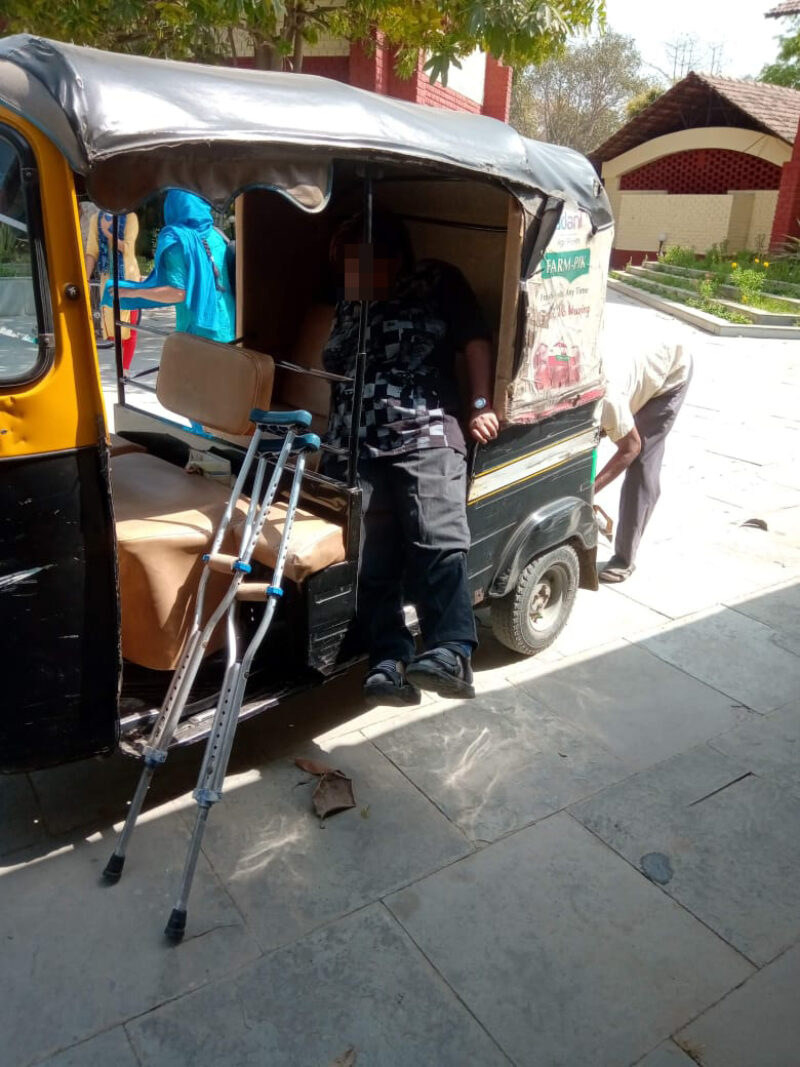 A person with physical disability getting into an auto rickshaw