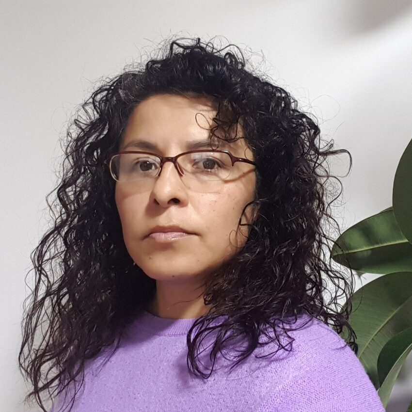 Photo of Dafne with loose curly black hair and wearing eyeglasses.