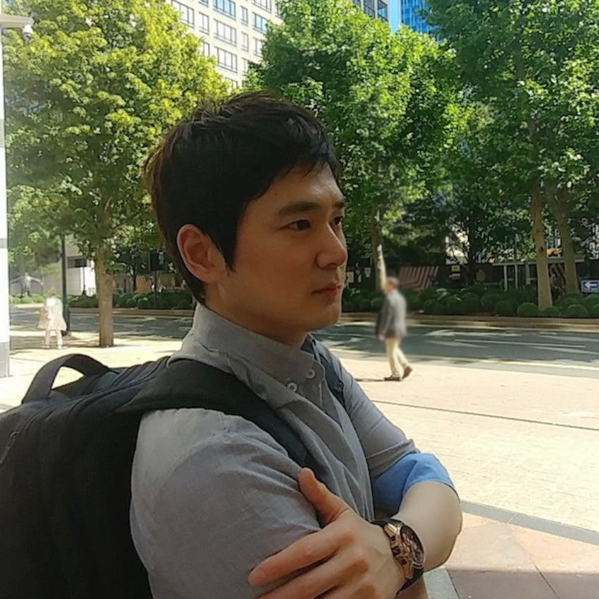 Dr Youngjun Cho looking away from the camera with arms folded. Trees and buildings in the background.