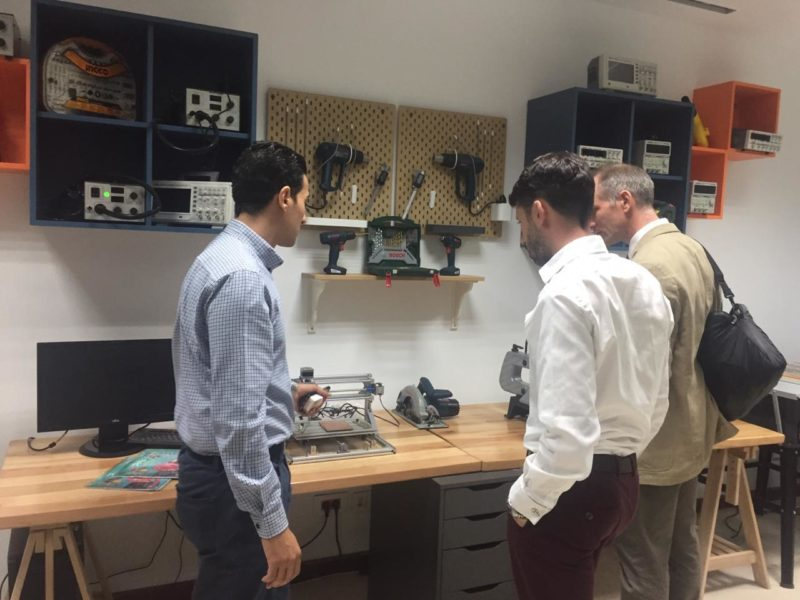 Iain and Tim being shown a work station of tools.