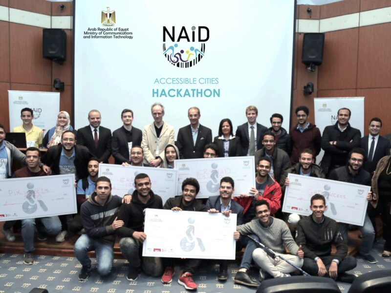Group picture of judges, organisers and hackathon participants smiling and holding giant cheques with prizes.
