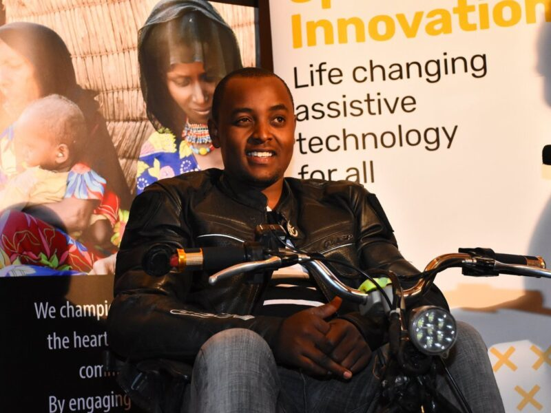 """Lincoln, a young black man, wearing a leather jacket and sat astride a motorcycle at an event. Poster stands are behind him - one partially reads """"Innovation. Life changing assistive technology for all"""""""