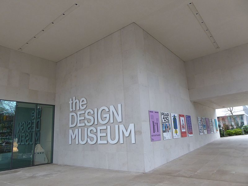 The front entrance of the Design Museum, A concrete building with the glass door on the left, the name central and colourful posters going off to the right.