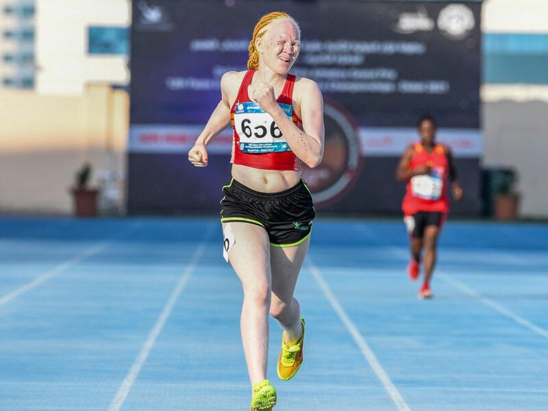 Monica Munga, a Para athlete from Zambia running on blue track