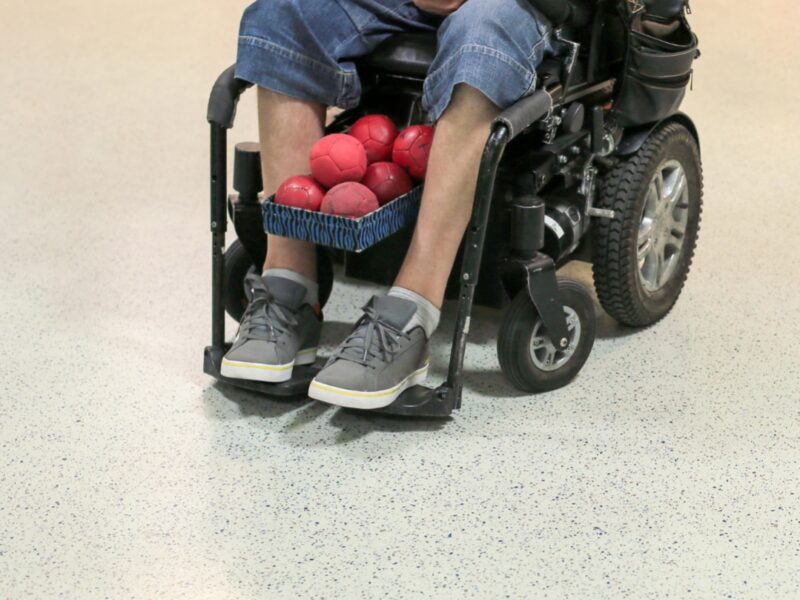 A basket of red tennis balls held together by a wheelchair user