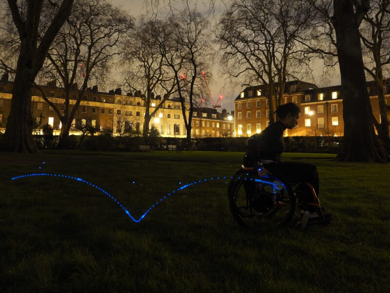 A view of a park in London at night. A manual wheelchair user is propelling a wheelchair in this park. The wheelchair user is wearing an inertial sensor in the wrist, a second one is attached to the wheel. A trail of blue light shows the trajectory that the sensor measures from a couple propulsions of the wheelchair.