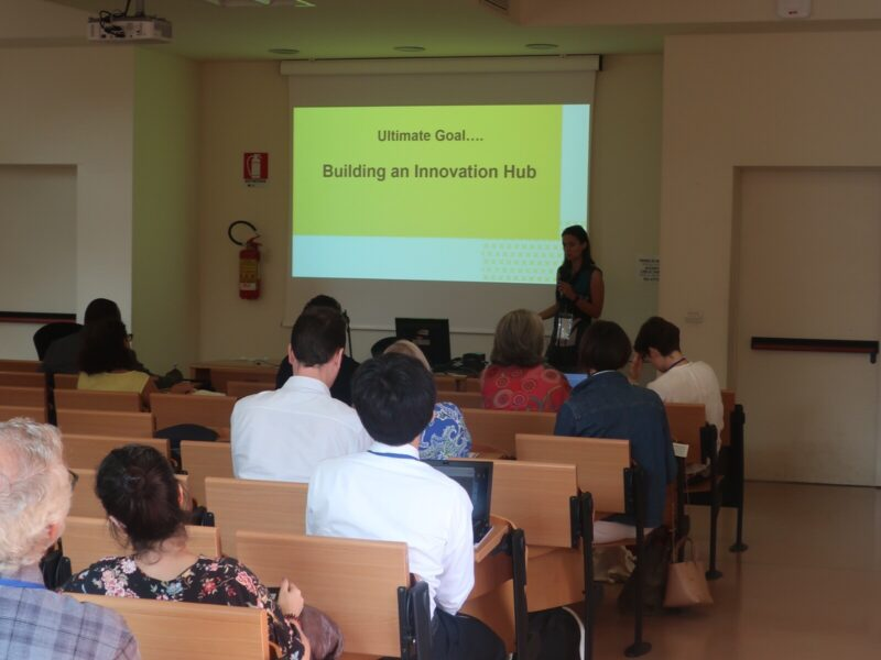 Giulia presenting in a lecture room. Screen shows projection of a PPT presentation