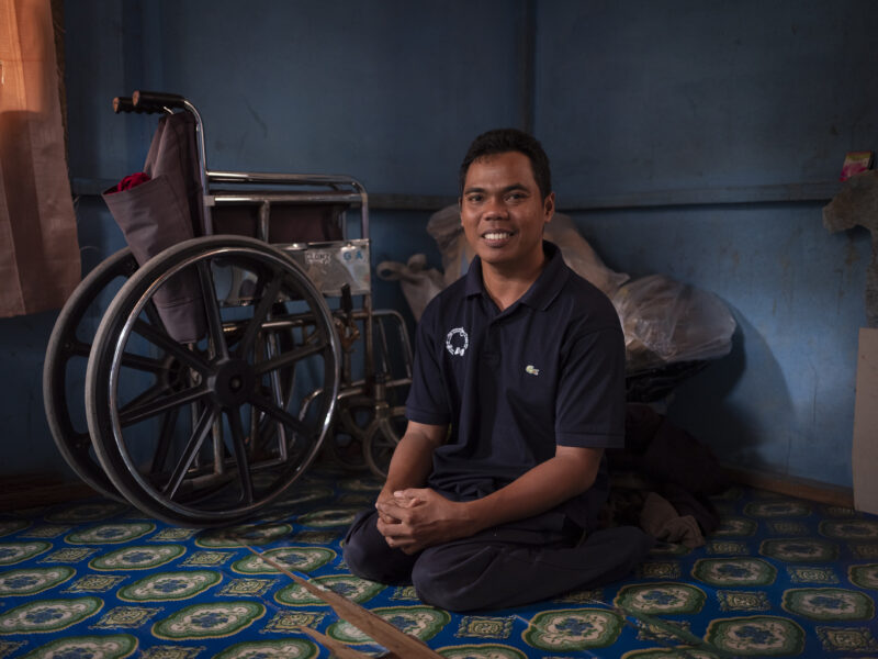 A man sitting in front of a folding wheelchair