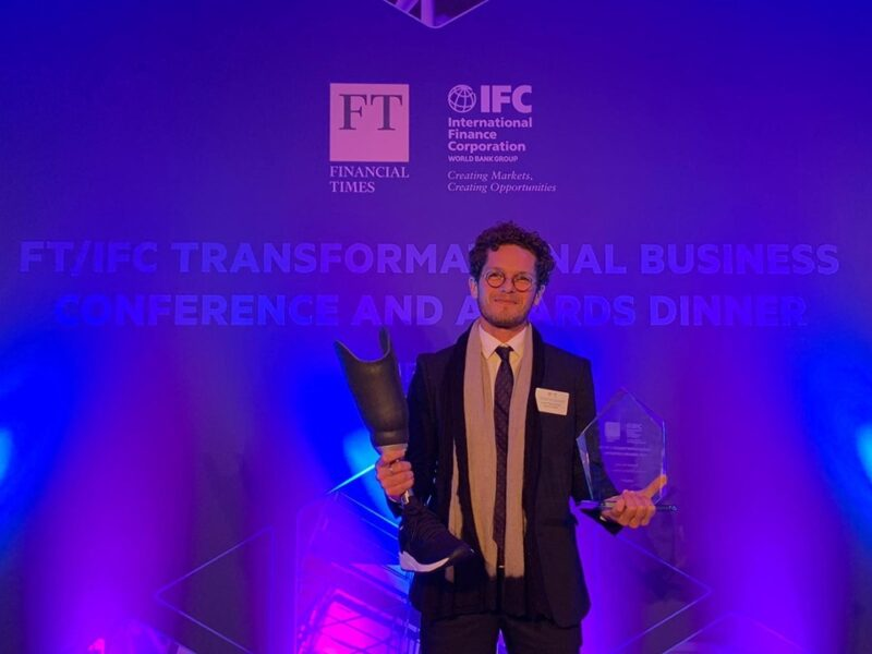 Lucas Melo, CEO of Amparo holds a prosthetic device and the FT/IFC award.