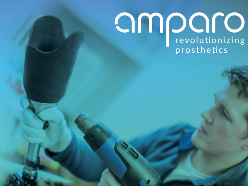 """An innovator is heating the socket of a prosthetic leg using a heat gun. On the top right corner is the logo of the company """"Amparo"""" with the phrase revolutionizing prosthetics"""