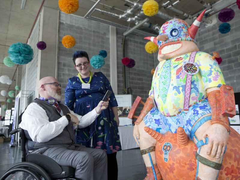 Women standing and man in wheelchair using a mobile device next to an art sculpture