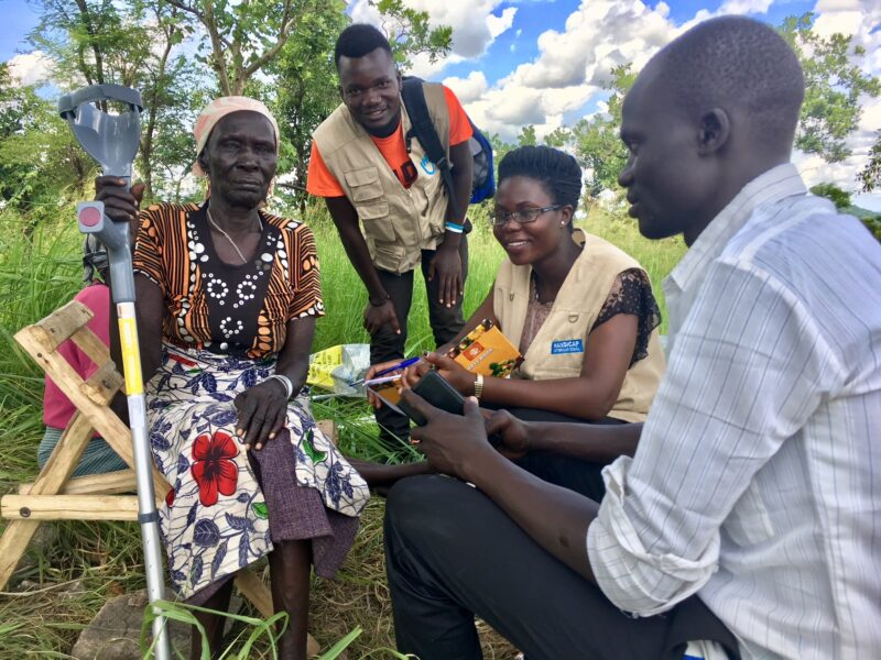Three young operators working for Humanity and Inclusion in Uganda assessing an elderly woman who uses a crutch