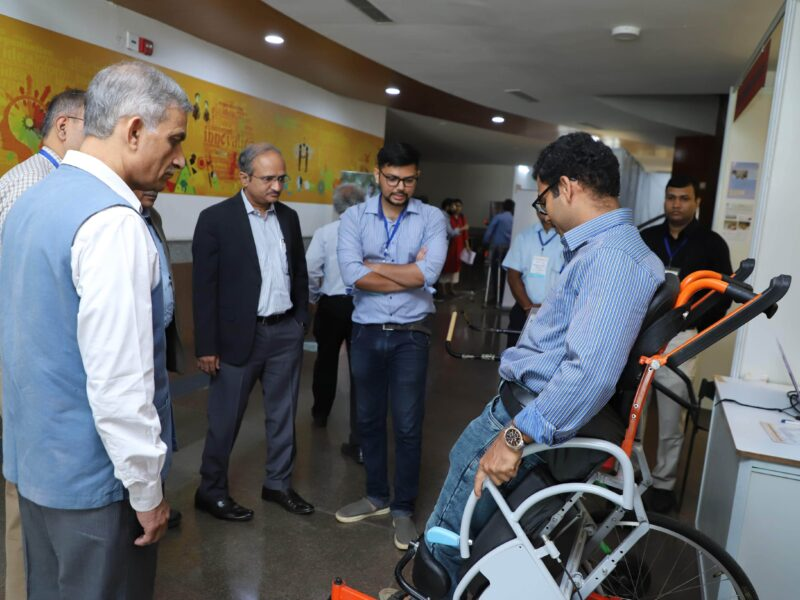 Group of people gathering around the prototype of the standing wheelchair.