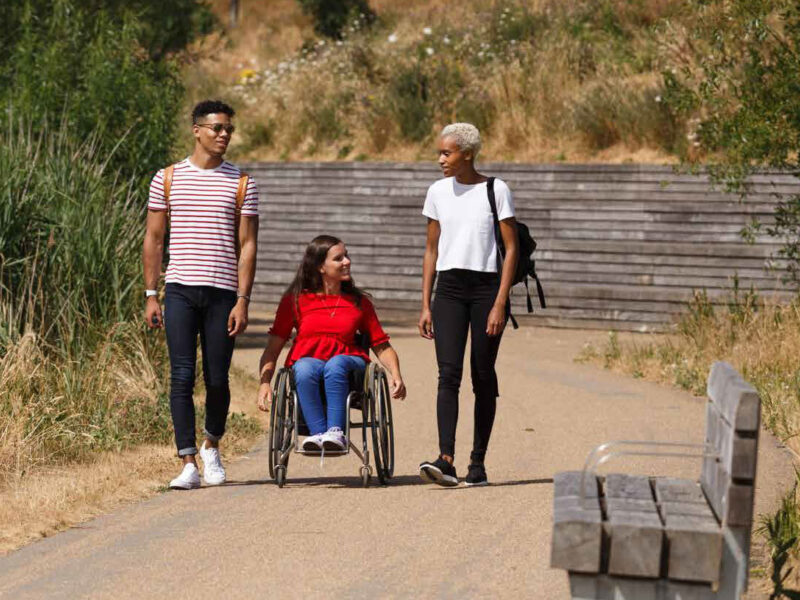 3 people strolling through the olympic park. Central person is a wheelchair user.