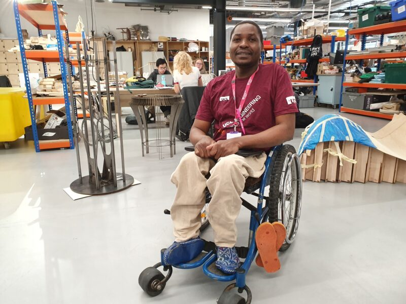 Wheelchair user sitting in front the workshop at UCL HereEast. Students working in the background.