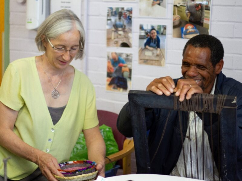Sarah Anton and Shadrek Ndlovu smiling and weaving on a loom