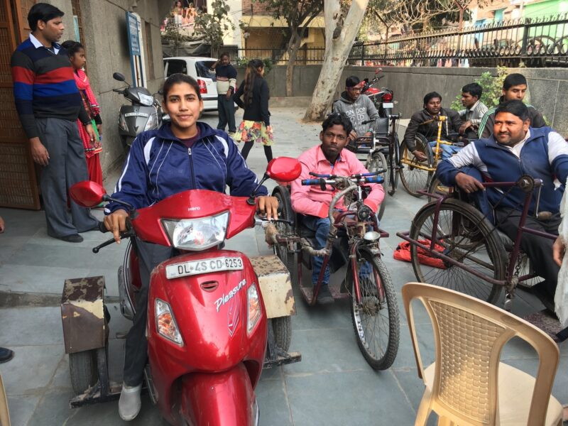 A busy street scene in India showing a broad range or motor and manually powered wheeled transport for disabled people