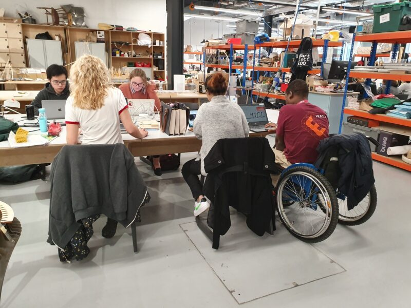 Five students seating by a workshop table at UCL Here East. One of them is a wheelchair user..