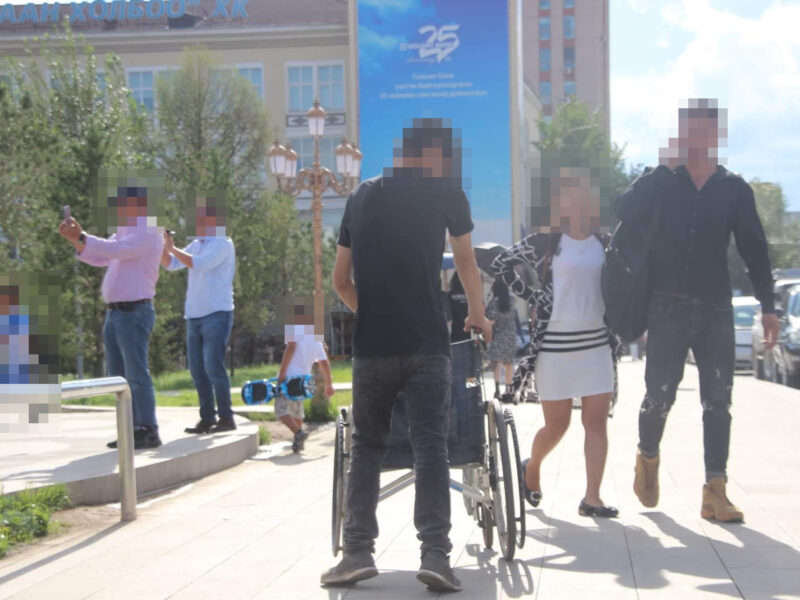 Wheelchair user and other people on the sidewalk
