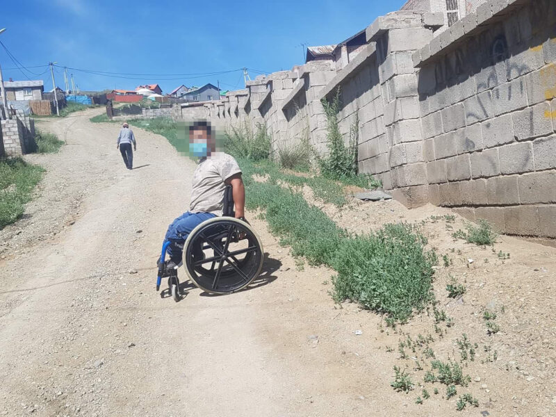 A person on a wheelchair on an uneven rocky path with grass patch and walls along the path