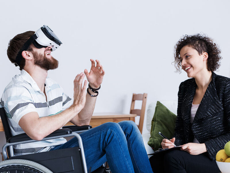 Male wheelchair user trying VR lenses. He is next to a woman that smiles to him while holding a pen.