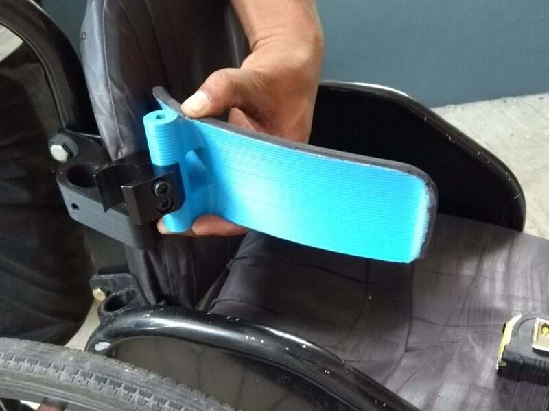 A technician is placing a 3D printed lateral postural support to the backrest of a wheelchiar