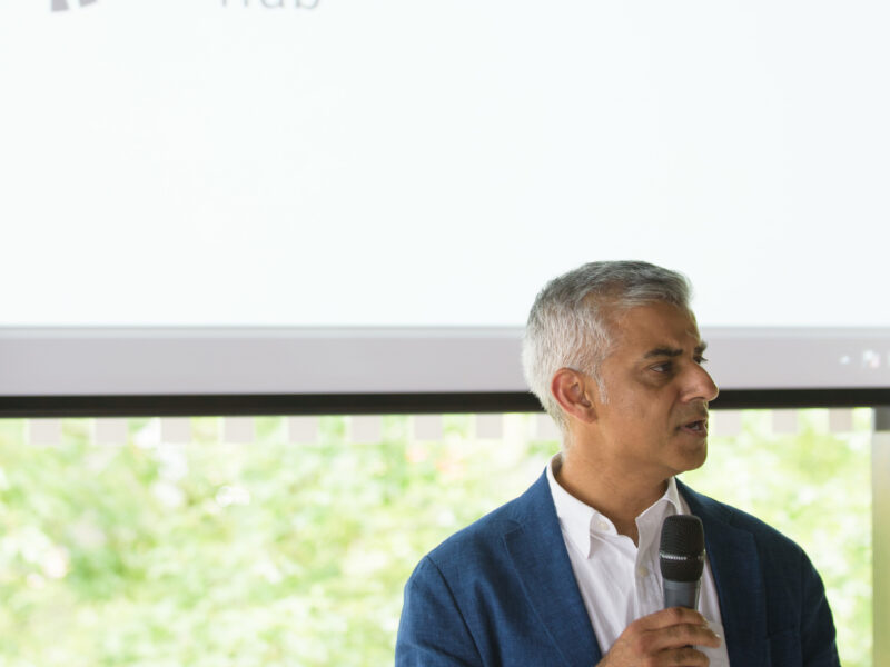 Mayor of London, Sadiq Khan, standing in front of GDI Hub logo holding a microphone as he launches GDI Hub at the launch event.