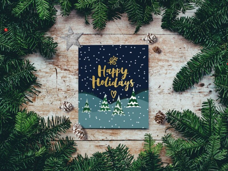 Happy Holidays card surrounded by pine