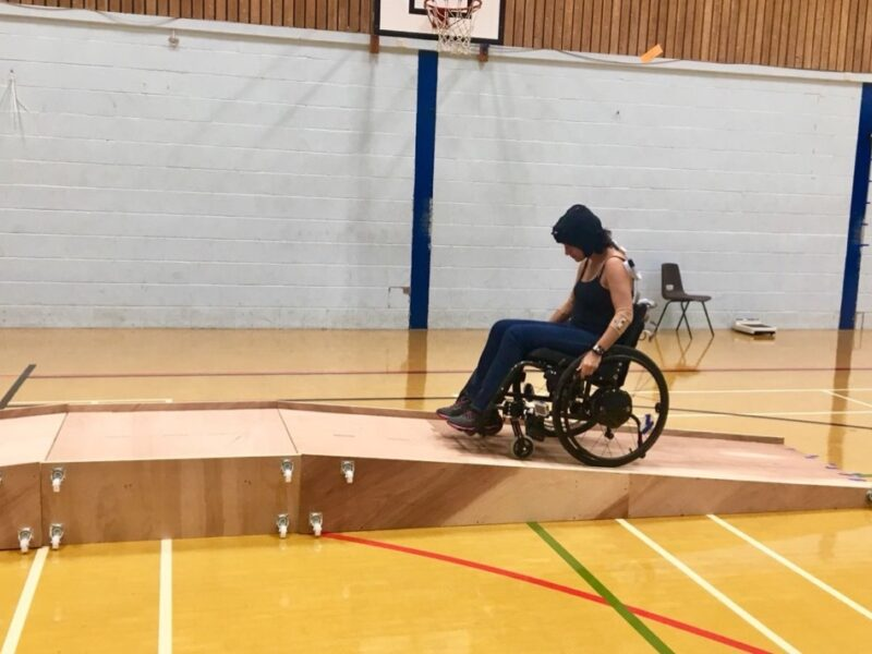 A female wheelchair user in dark clothes and beanie hat ascending a ramp from right to left in a sports hall.