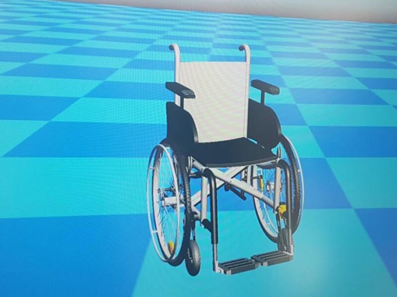 A computer generated 3D model of a wheelchair on a blue chequered background.