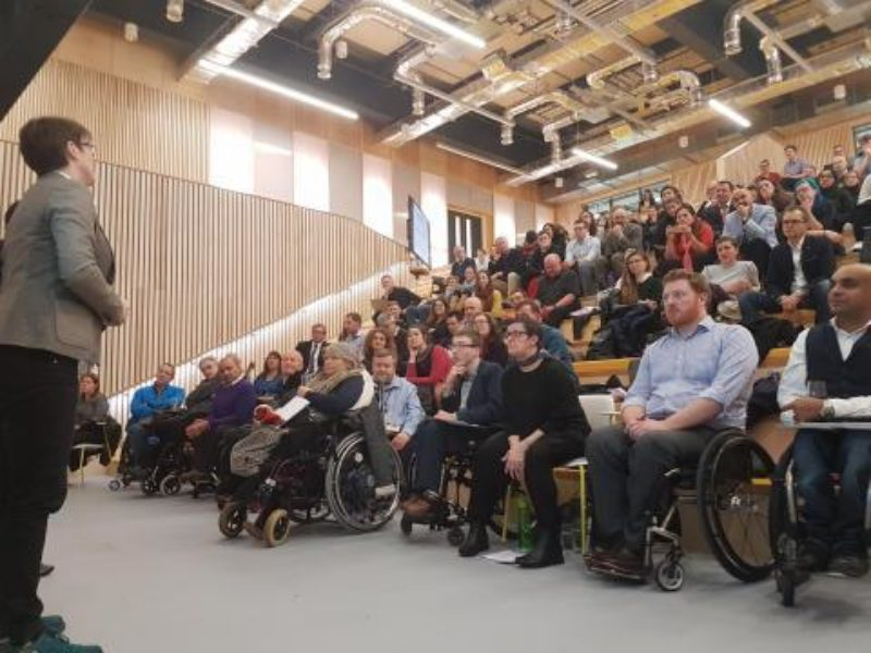 Catherine Holloway standing on the far left delivering a lecture to a full auditorium, there are many wheelchair users in the front row.