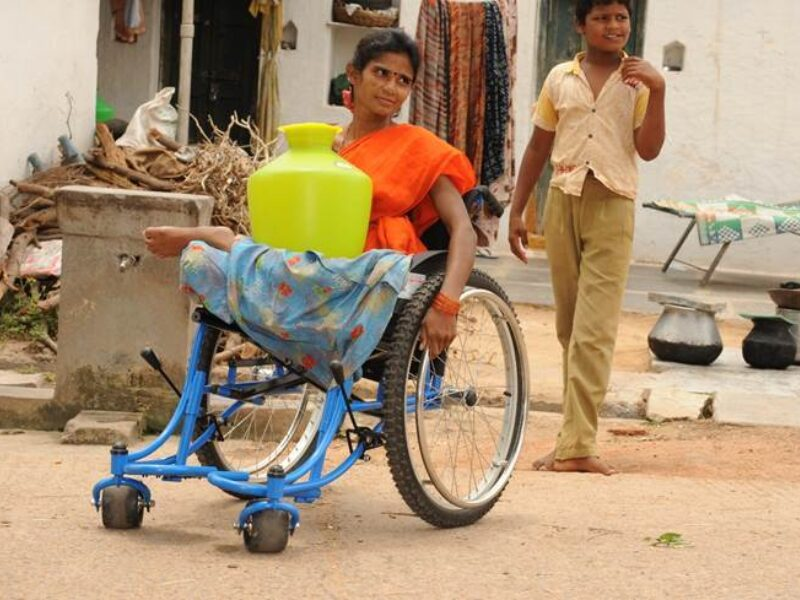 Lady in a wheelchair, wearing a bright orange top, holding a yellow water jug; a boy follows behind. They are in a street in India.