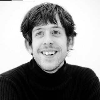 Black and white headshot of Mark Carew