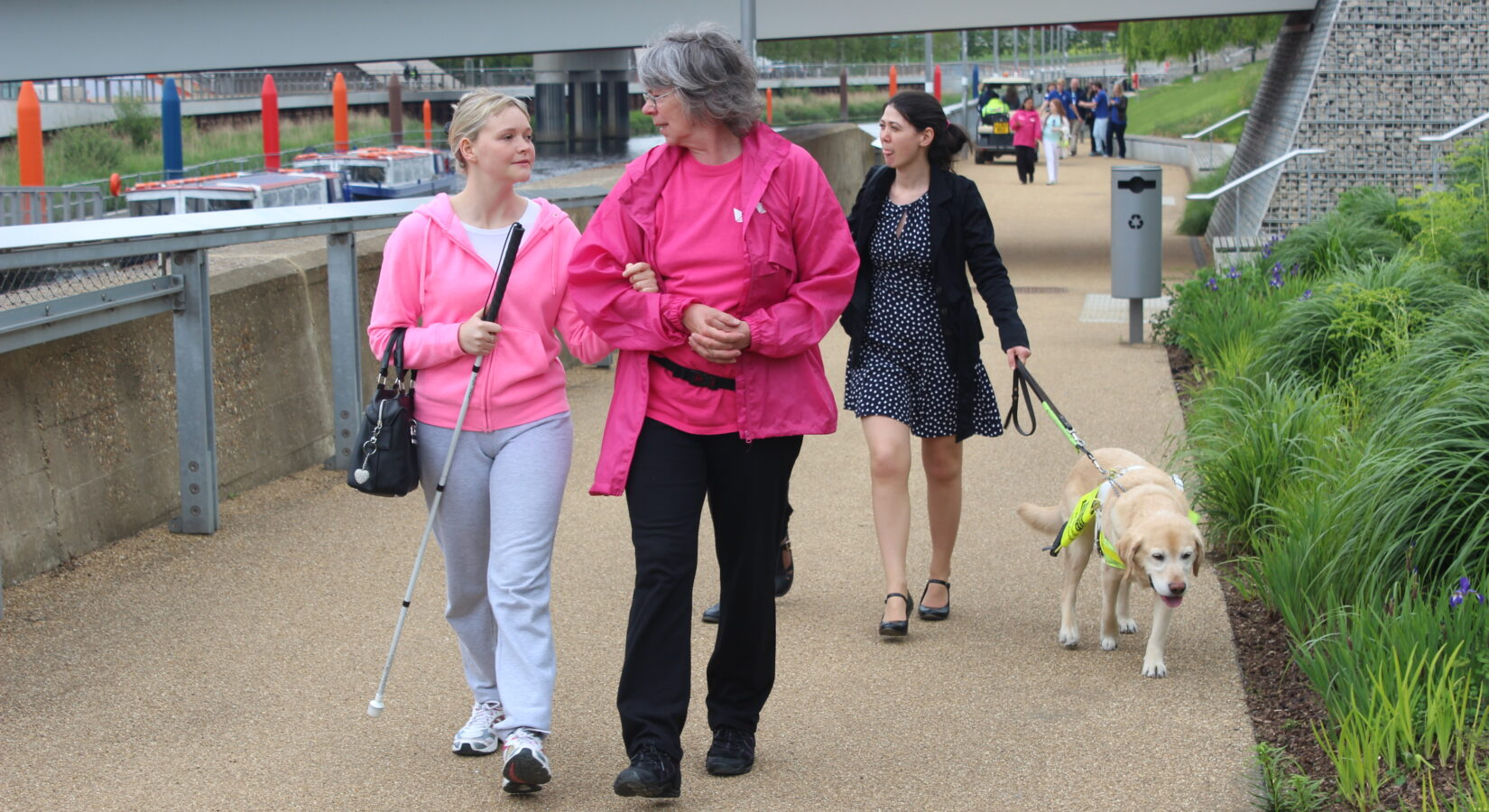 Image shows a Park Champion volunteer on Queen Elizabeth Olympic Park providing a sighted guide service to a visually impaired visitor.